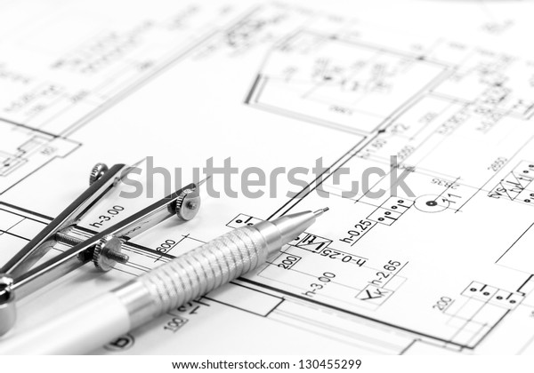 Drawing compass and pencil on house floor plan