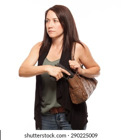 Drawing gun from holster in her concealed carry purse | Attractive female shooter holding weapon against white background.