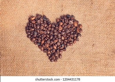 Drawing a heart from coffee beans on burlap. Vintage style.