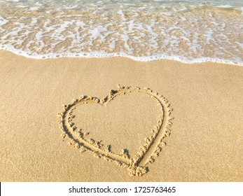 A drawing of a heart on wet beach sand at a beautiful seascape background. Texture.