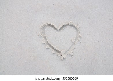 drawing heart symbol on sand beach for background