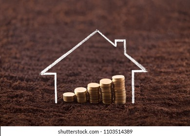 Drawing house with growing coins on fertile soil land