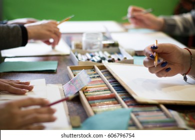 Drawing lesson for children and adults. Pastel pencils. Beautiful pastel picture. many people. Box with pencils on the table. Many materials.