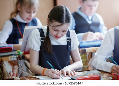 Drawing lesson in an elementary school. The girl carefully paints with a brush on a piece of paper. The concept of primary education.