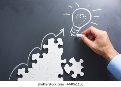 Drawing light bulb on blackboard. Steps shaped jigsaw puzzle. Concept image of developing new idea.