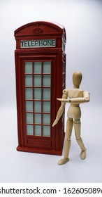 Drawing mannequin walking past model of UK red Phone Booth