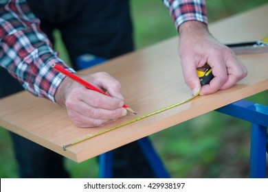 Drawing a melamine panel with a square and a pencil outdoor