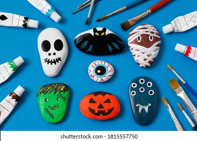 Drawing on stones Halloween characters. Art project for children. DIY concept. Halloween party decor. Skull, bat, mummy, stuffed animal, eye, pumpkin, monster painted on sea stones