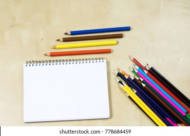 Drawing pencils and a sketching notebook on a wooden table. Sketchpad on the drawing board. White background
