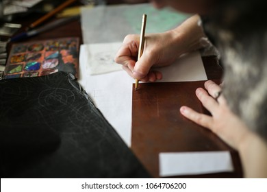 drawing a sketch on a plate of copper with a metal pen, close-up, materials in a home creative workshop, the concept of creativity and soft focus, toning and lifestyle