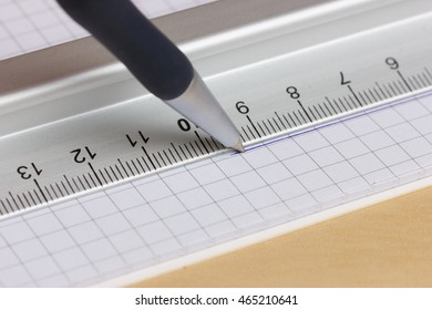 Drawing straight line with pen and ruler in exercise book