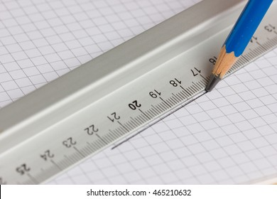 Drawing straight line with pencil and ruler in exercise book