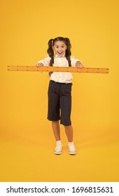 Drawing straight lines at geometry. Happy small girl holding ruler for geometry lesson on yellow background. Little child learning geometry. Cute schoolchild preparing geometrical tool for geometry.