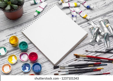 Drawing tools, stationary supplies, workplace of artist. Watercolor paints and blank notepad on  wooden desk