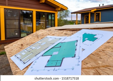 Drawings of the building next to the finished cottage. Architectural and construction drawing. Concept - construction site. Concept preparation for finishing work. Pulan at home on paper.