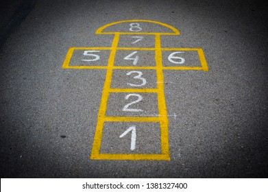 Drawings on the asphalt in the school for children's play. Hopscotch court with numbers from 1 to 8 drawn with white paint on the asphalt.Child playing hopscotch game.