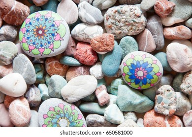 Drawings on the rocks. Pebble painting. Colored stones.