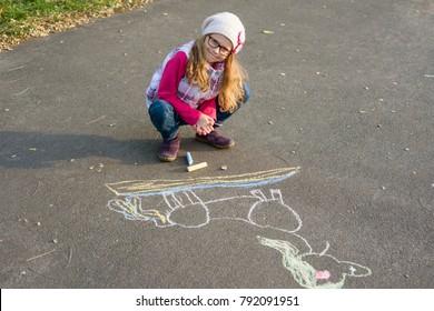 Drawings on the sidewalk, girl child draws a unicorn