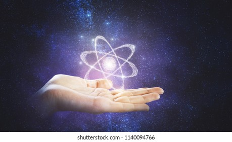 drawn atom model above man hand at abstrac tgalaxy background