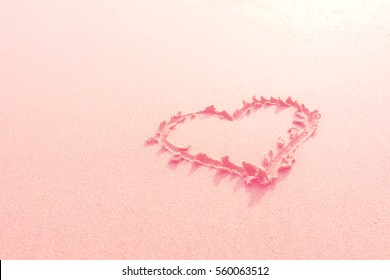 Drawn heart on beach. filtered pink style