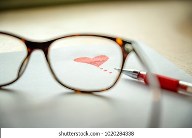 Drawn Heart picture and placed red pen on paper looking through from eyeglasses lens