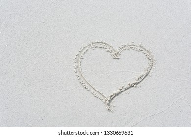 Drawn love heart shape on white sand beach background