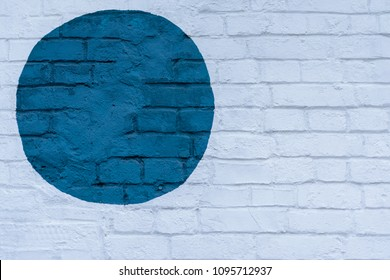 Drawn painted blue circle on a light brick wall bricks surface of wall, as graffiti. Graphic abstract modern background. Modern iconic urban culture, stylish pattern