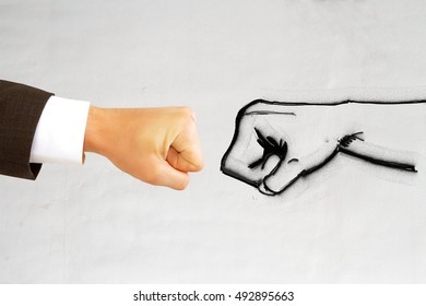 Drawn and real humans fists against each other on light background. Strength concept