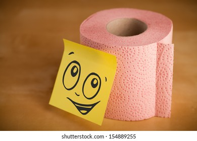 Drawn smiley face on a post-it note sticked on a toilet paper