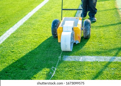drawn white lines on the football field with white paint on the grass using a special machine before a game