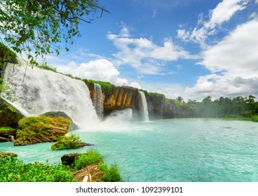 The Dray Nur Waterfall on the Serepok River among green woods at the Tay Nguyen (the Central Highlands) in Dak Lak Province (Daklak) of Vietnam. Scenic summer landscape with azure pond and blue sky.