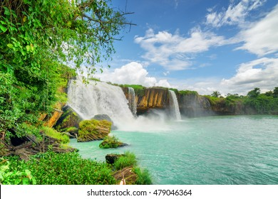 The Dray Nur Waterfall on the Serepok River among green trees at the Tay Nguyen (the Central Highlands) in Dak Lak Province (Daklak) of Vietnam. Amazing summer landscape with azure pond and blue sky.