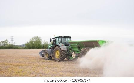 Draycott, Derbyshire, UK, 04/24/2018, a green tractor spreading dust fertilizer on a field.