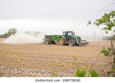 Draycott, Derbyshire, UK, 04/24/2018, a John Deere tractor spreading ash dust fertilizer on a field.