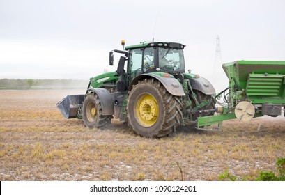 Draycott, Derbyshire, UK, 04/24/2018, a John Deere tractor spreading dust fertilizer on a field.