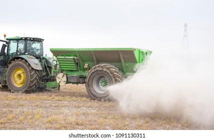 Draycott, Derbyshire, UK, 04/24/2018, a John Deere tractor spreading dust fertilizer ash on a field.