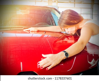 Dream about car. Gorgeous smiling woman kissing hood of new red car in the dealership.