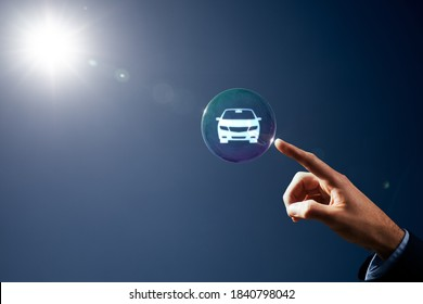 Dream about new car, carsharing, car rental and leasing concepts. Hand with soap bubble (symbol of dream) with symbol of the car inside.