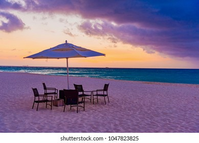 "dream beach at sunset on the Caribbean sea with palm trees and chairs on the island of Aruba in the Dutch Antilles ""Eagle Beach"""