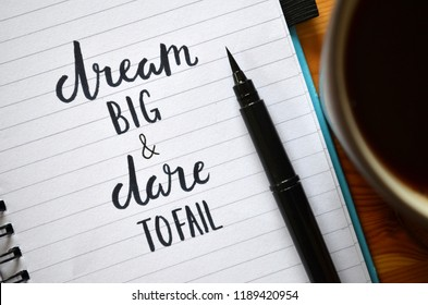 DREAM BIG AND DARE TO FAIL written in notebook with cup of coffee and pen