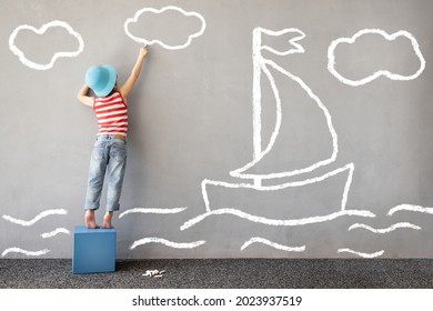 Dream big! Happy child playing outdoor. Funny kid draws a chalk sea on the wall. Child dreams about travel. Kid pretend to be captain. Children imagination and summer vacation concept