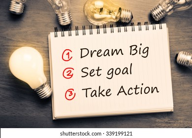 Dream Big - Set Goal - Take Action, handwriting on notebook with light bulbs