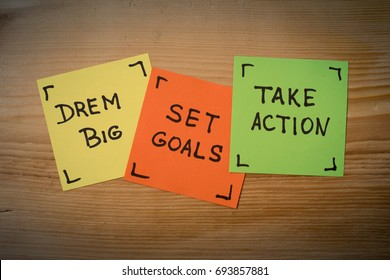 Dream big, set goals, take action, success recipe on wooden background. dream big, set goals, take action - motivational advice or reminder on colorful sticky notes against rustic wood
