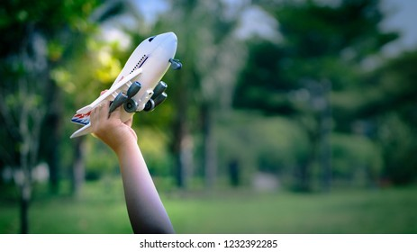 Dream of boy with toy airplane flying over sky, creative kid thinking concept.