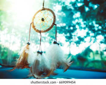Dream catcher hanging in front of the car along the road with orange light and bokeh blur background
