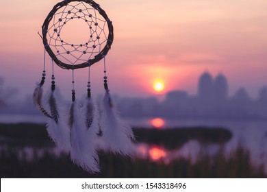 Dream catcher on the background of the river and the city. Out of town, in nature. Far from the city. Sunrise or sunset.