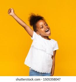 Dream come true. Cute african toddler girl shouting hooray, gesturing hand up on orange studio background