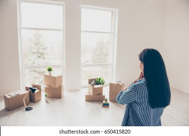 Dream come true! A start of new life! Brunette woman moved in to new light and modern apartment. She is looking at boxes with her belongings, planning how she will organize the space here