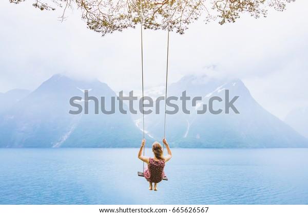 концепция мечты, красивая молодая женщина на качелях в фьорд Норвегия, вдохновляющий пейзаж