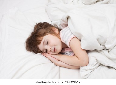 A dream day for a child. A girl of 4 years is sleeping on the bed. An empty space to insert text.